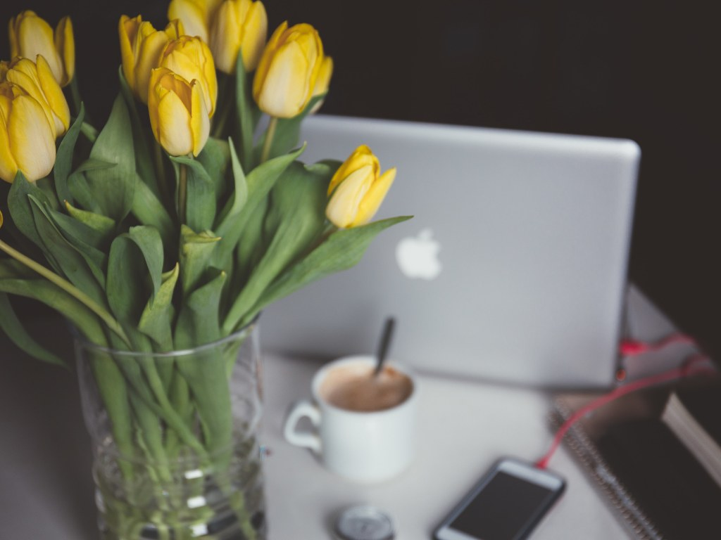 1024x768-209160-yellow-tulips-in-a-glass-vase-on-a-desk-with-a-lap